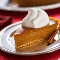 Vegan pumpkin pie with dairy free whipped cream and cinnamon sticks on holiday table