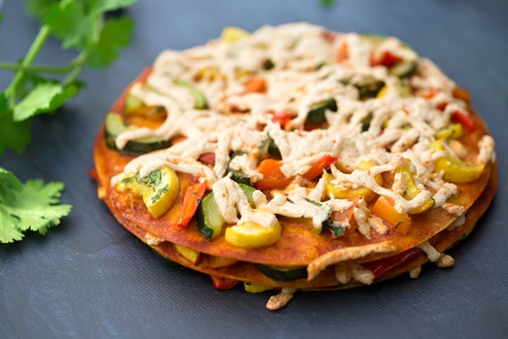 Stacked vegan squash and bell pepper enchiladas