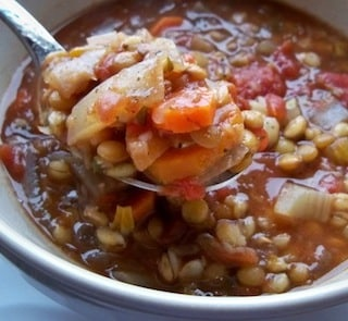 Tomato, lentil, and barley soup in a spoon