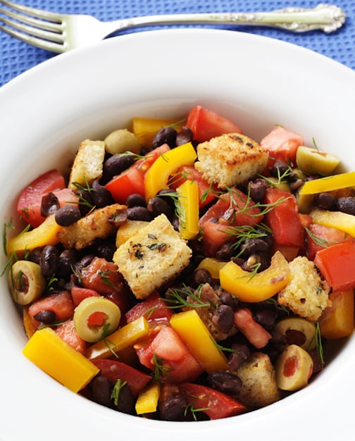 black bean salad with tomatoes, croutons, and olives cropped recipe