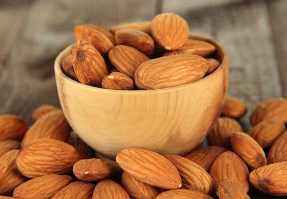Whole almonds in a wooden bowl