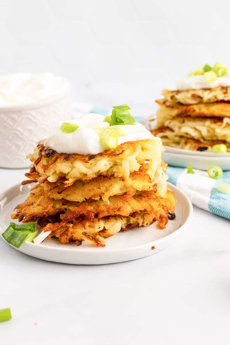 plate of stacked vegan potato pancakes topped with sour cream and green onions