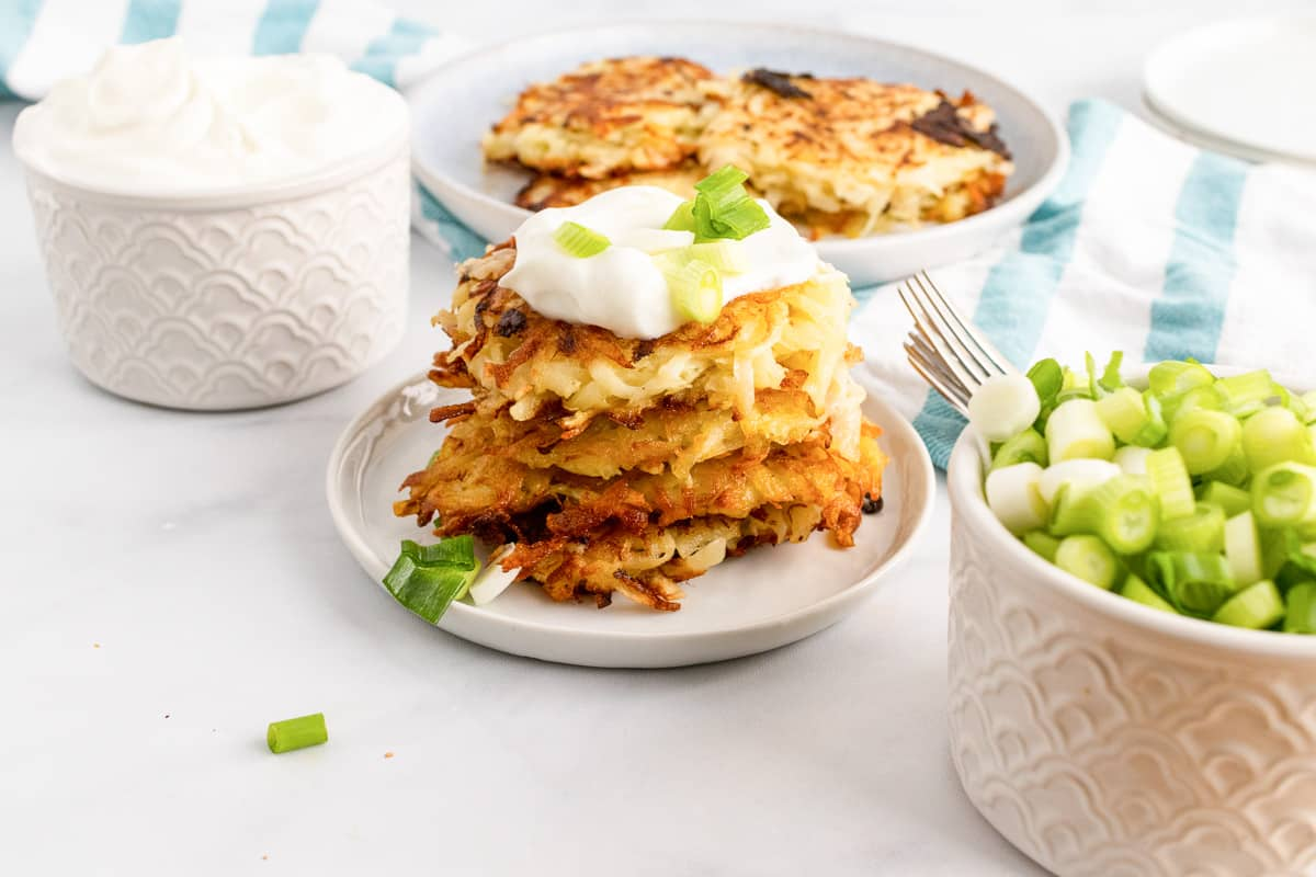 stack of vegan potato pancakes on plate neat bowls of toppings and more pancakes