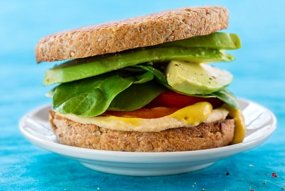 Hummus avocado and baby spinach sandwich on English muffin