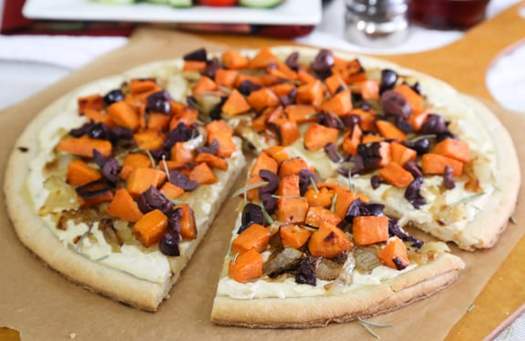 White vegan pizza with sweet potato, onions, and olives