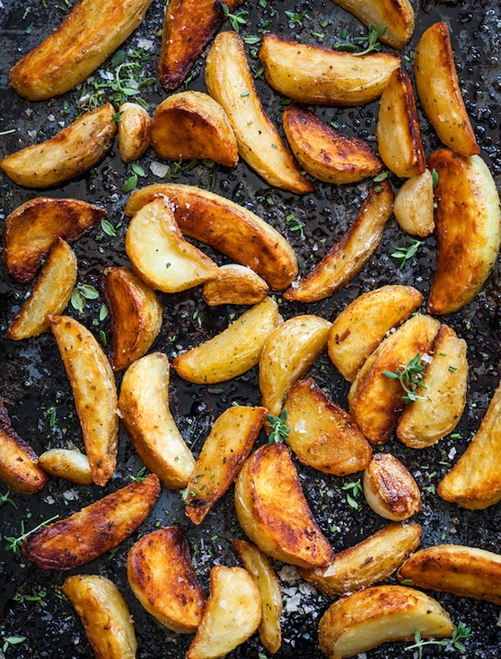 Roasted potato wedges on a baking tray
