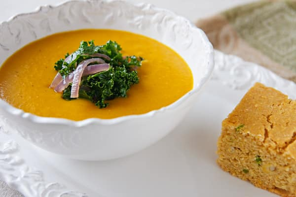 coconut butternut squash soup with fresh kale and onion garnish and cornbread side