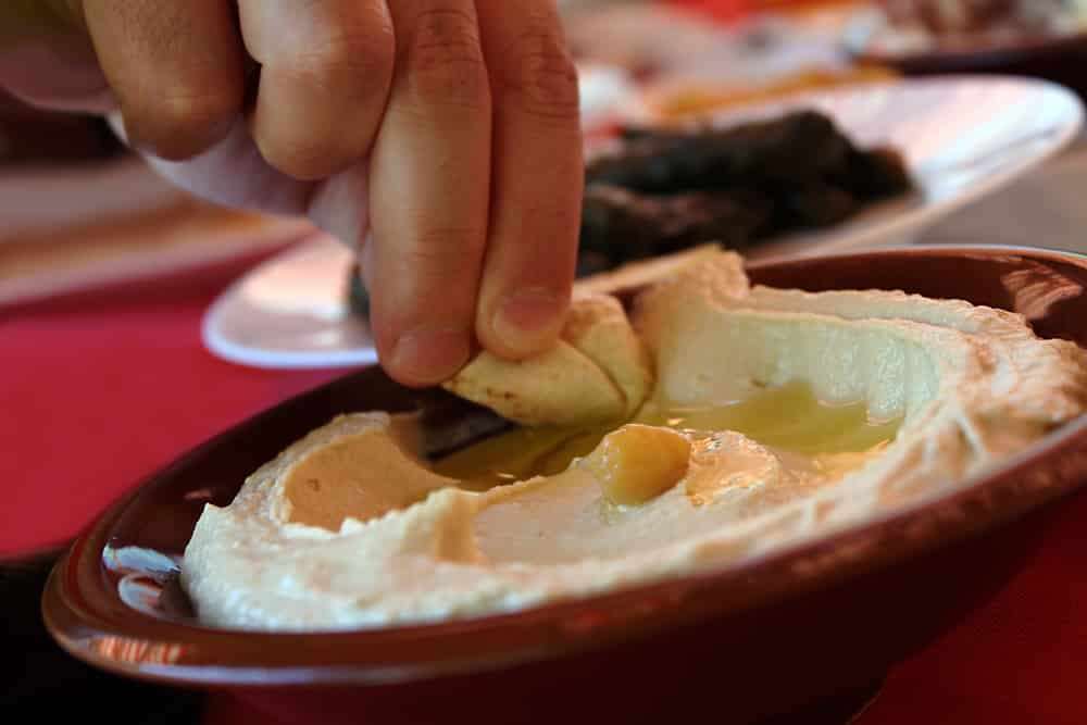 A man dipping a pita bread slice in a traditional hummus plate