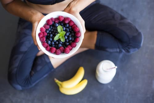 Above shot of a woman with a bowl of berries, a bottle of almond milk and two bananas wearing a sportive outfit.