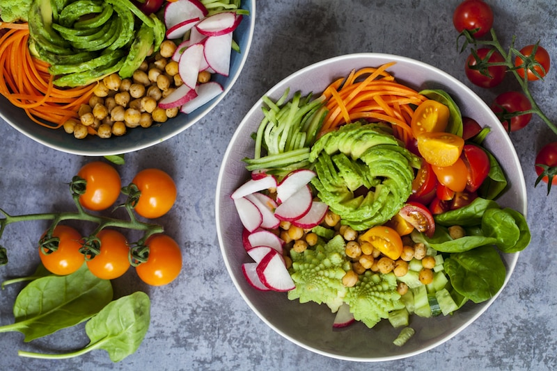 Buddha bowl of mixed vegetable with avocado, carrots, spinach, romsnesco cauliflower and radishes