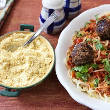 Vegan meatballs on pasta with vegan parmesan cheese