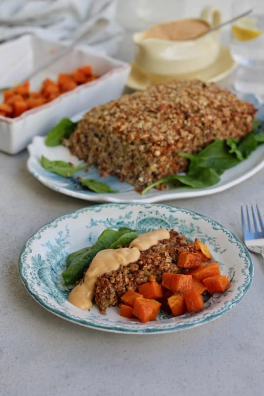 slice of thanksgiving nut roast on plate with roast in background
