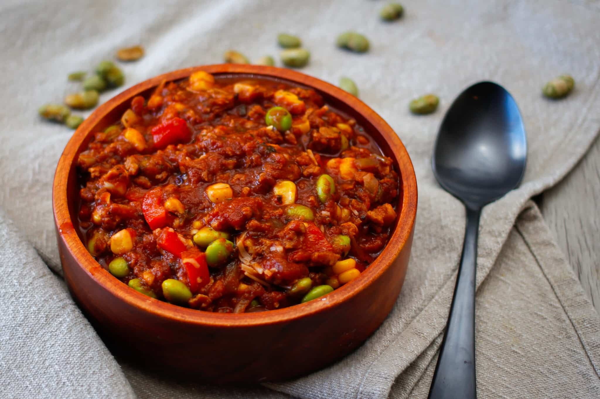 vegetarian chili with corn and soy beans in an orange bowl