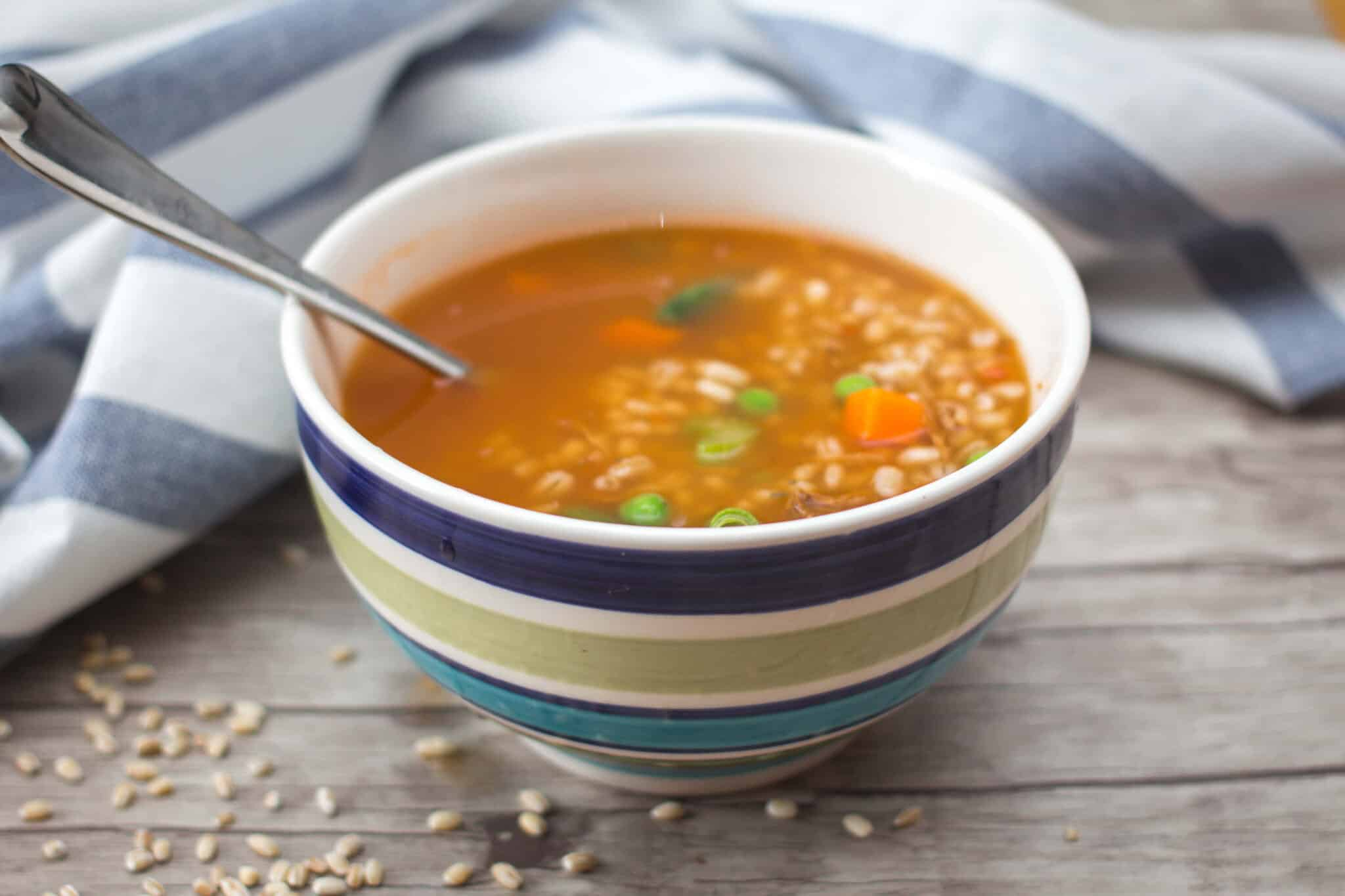 blue striped bowl of vegetable and barley soup on a table