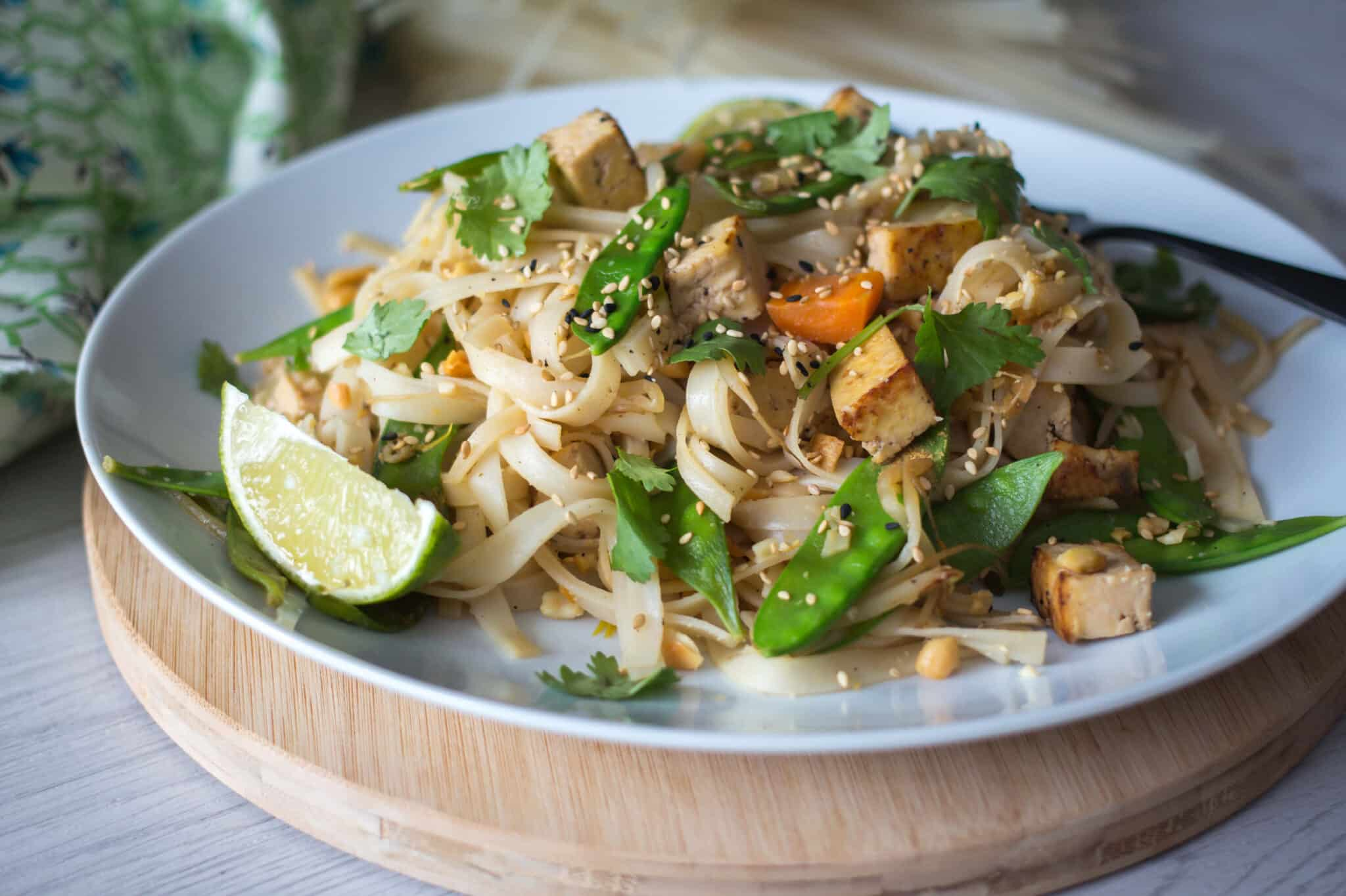 plate of vegan pad Thai on a wooden stand