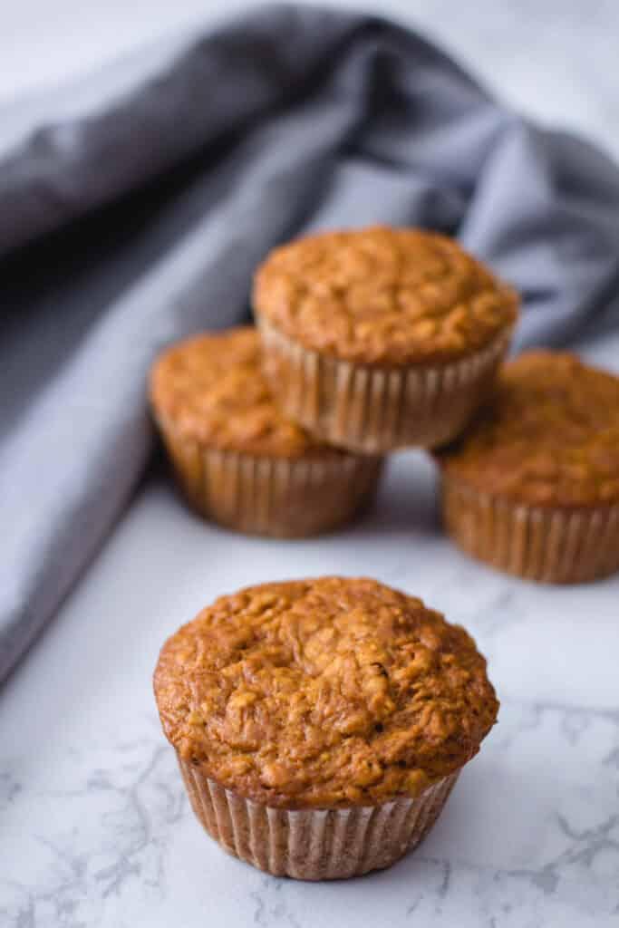vegan bran muffins stacked on a blue napkin