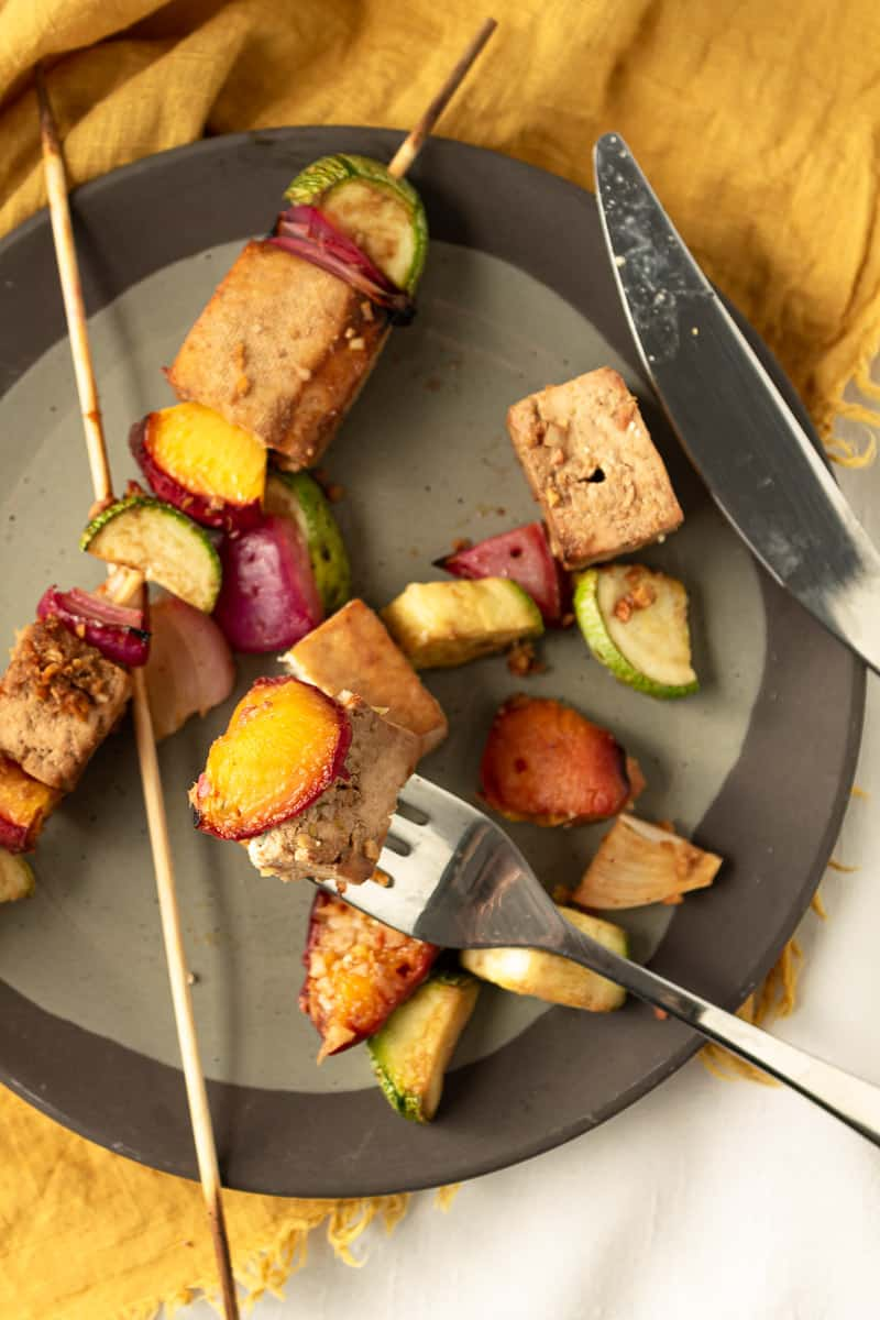 forkful of grilled tofu skewers over a plate