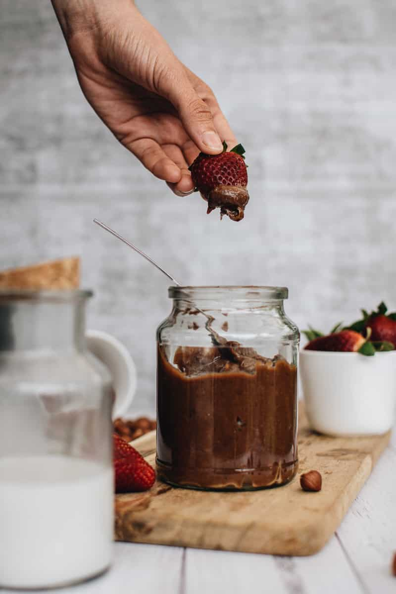 strawberry being dipped into jar of homemade vegan nutella