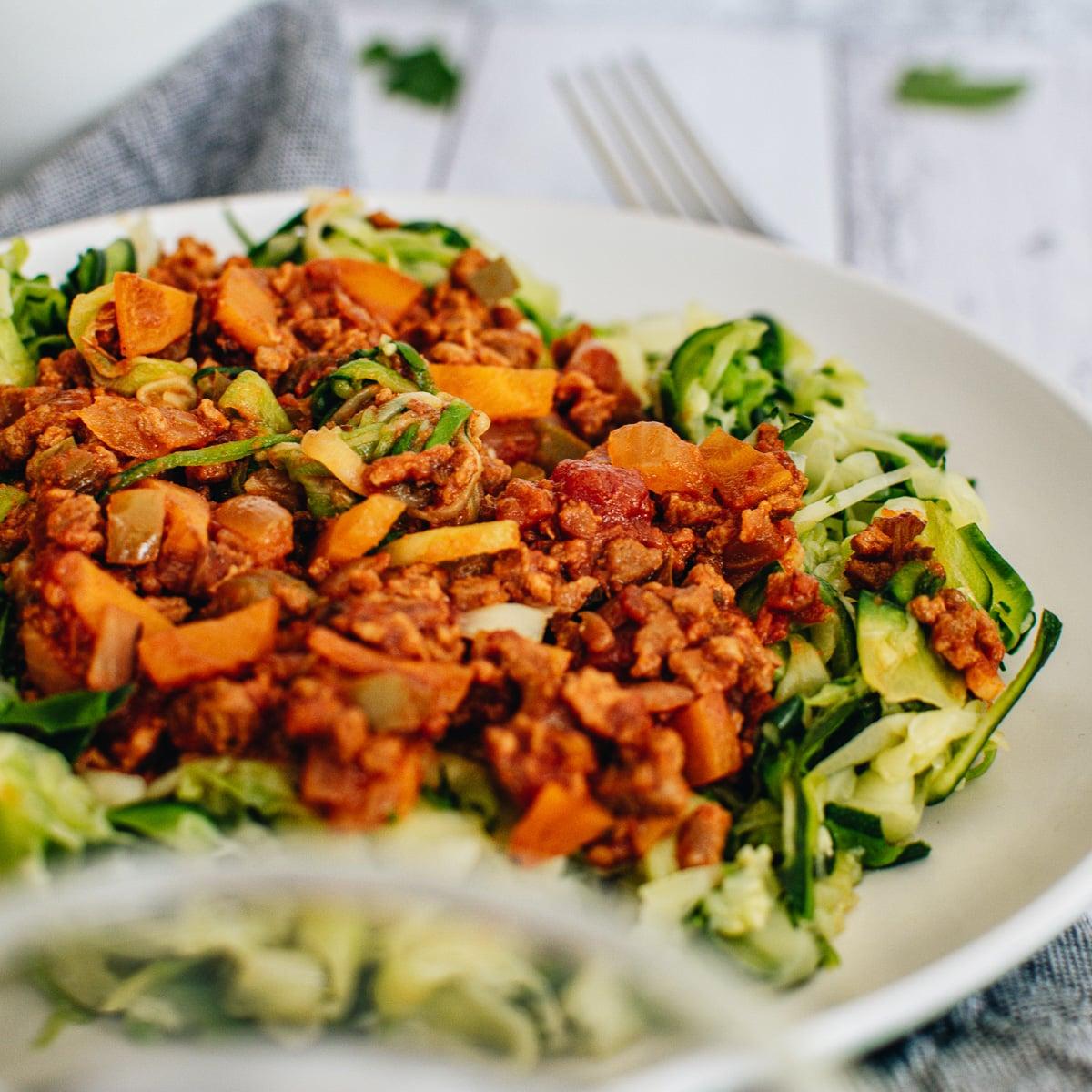 Cerrar fideos de calabacín veganos cubiertos con salsa boloñesa vegana