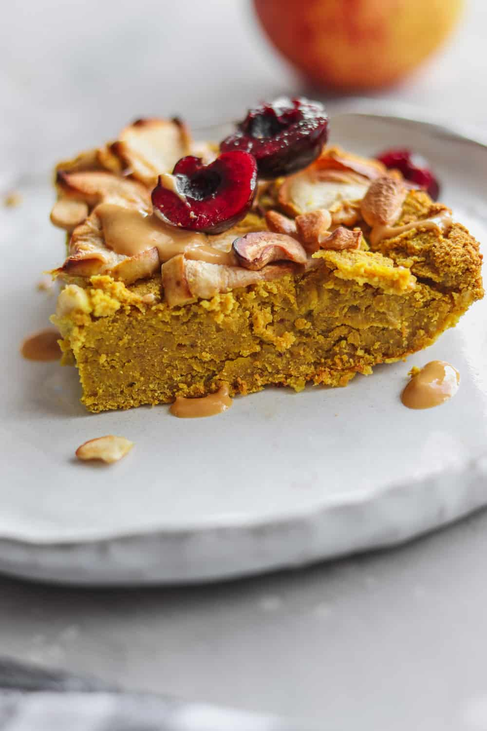 slice of chickpea cake topped with fruit and nuts