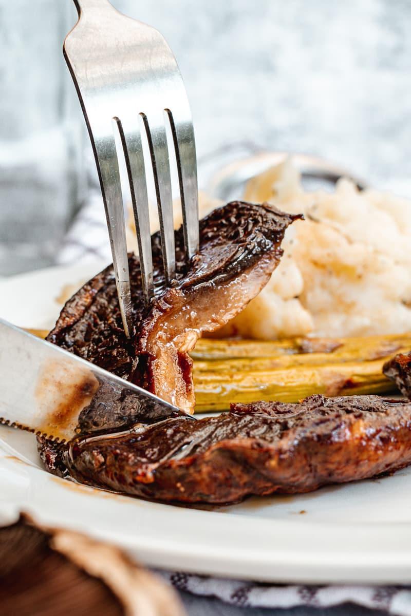 fork and knife cutting into a portobello mushroom steak
