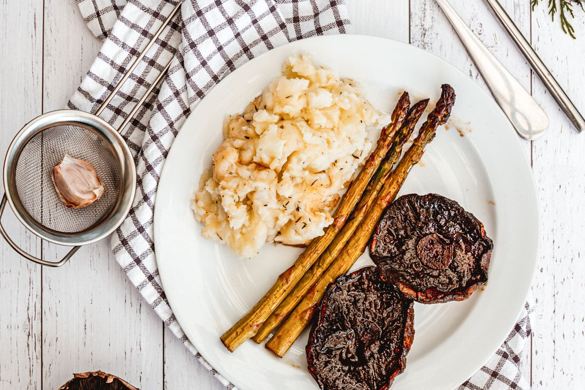 plate of vegan mashed potatoes with asparagus and portobello steaks