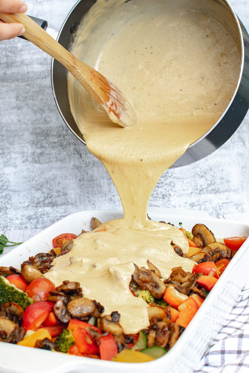 pouring vegan cheese sauce over roasted veggies