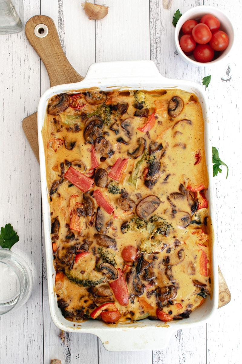 pan of roasted veggies with vegan cheese sauce